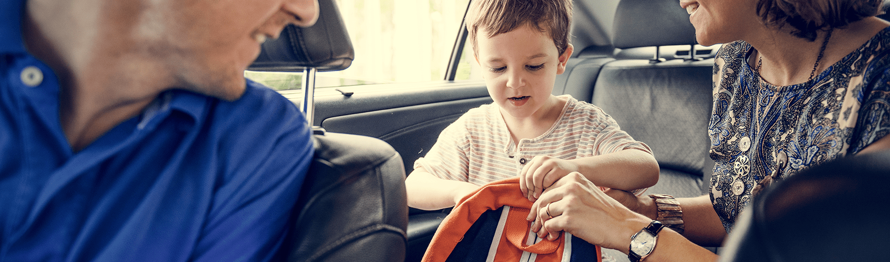 Motor Insurance: A family within their car, the parents helping their son with his backpack