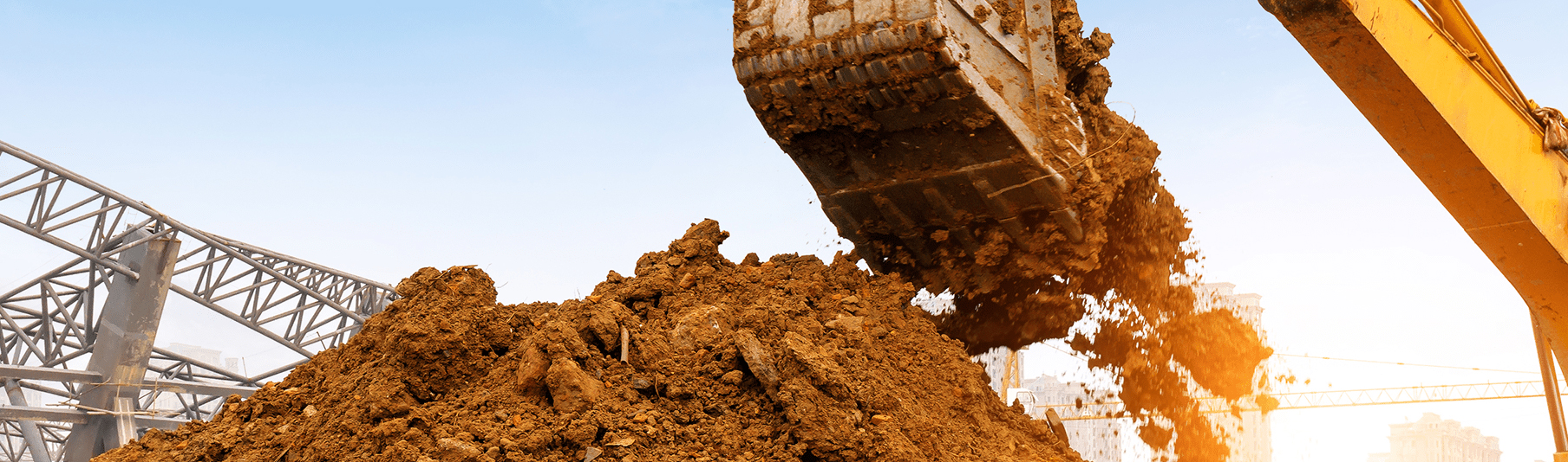 Construction Insurance: A large pile of dirt being scooped up by a bulldozer