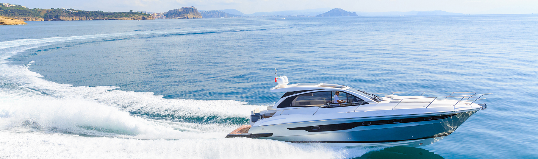 High Net Worth Insurance: A man driving a luxury speed boat across the sea