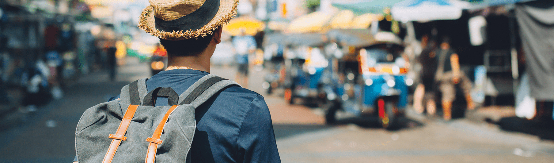 Travel Insurance: A man with a straw hat on his holiday, observing a busy market
